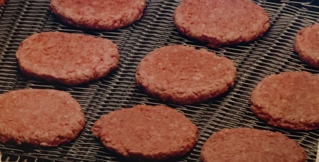Raw hamburgers on an Ultra Series Stainless Steel Mesh Overlay Belt